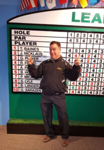 Writer Tim Baines having fun with the leaderboard at the World of Golf Hall of Fame